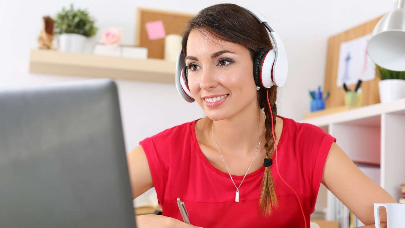 Woman on laptop with headphone taking an online course