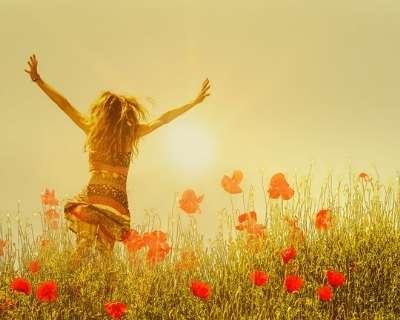 Woman running through poppy field in freedom pose