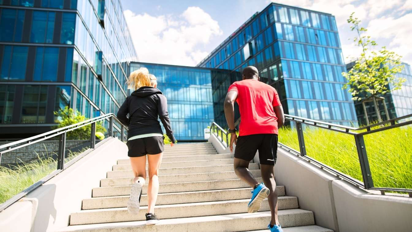 Man and woman running up steps towards office