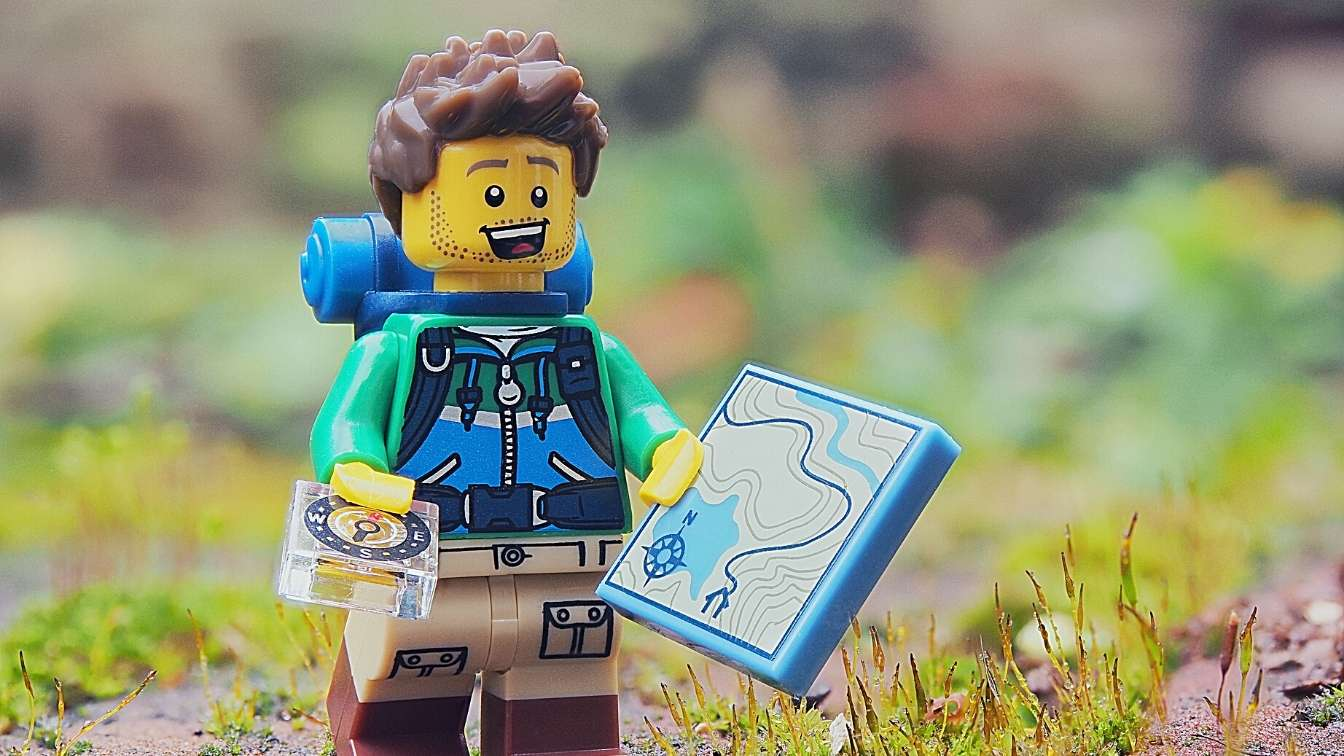 Lego man with map and compass starting on a journey