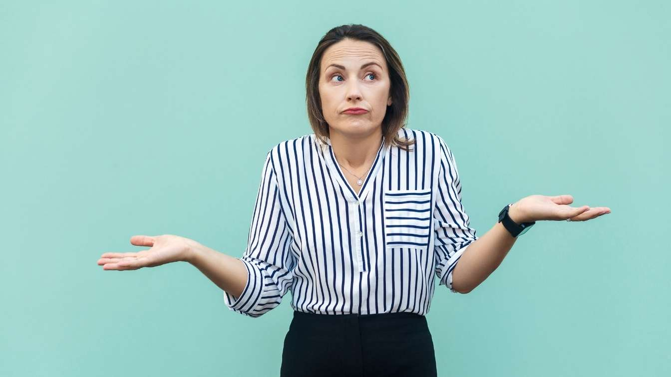 Woman with arms out shrugging on green background